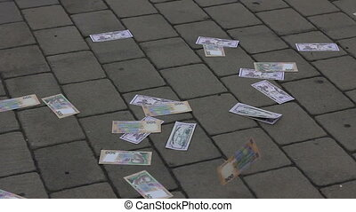 wind carries money on the street on belt tiles