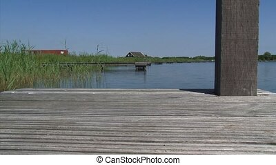 View from empty wooden pier at blue lake under blue sky -...