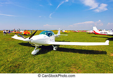White airplane on a green grass field