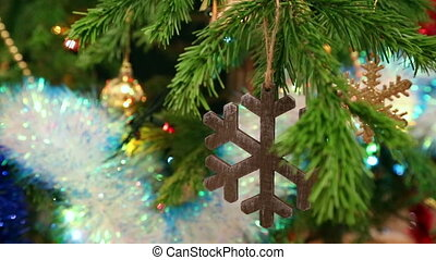 christmas wooden snowflake hanging on fir twig