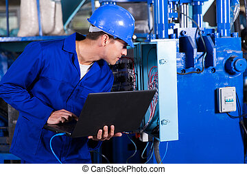 technician checking distribution box with laptop -...