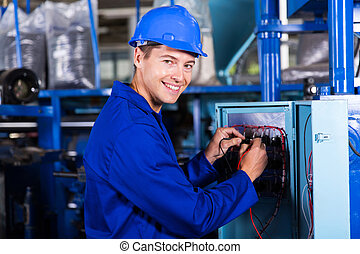 male electrician working on industrial machine