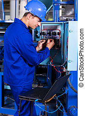 industrial engineer repairing computerized machine with...