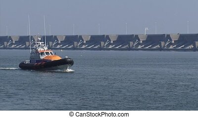 Dutch lifeboat KNMR sails in front of Haringvlietdam sea...