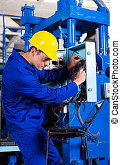 industrial technician repairing computerized machine