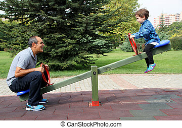 Happy family enjoying seesaw at the playground in the park