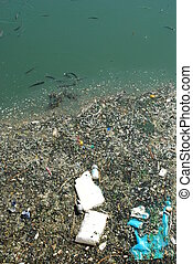 Polluted river full of rubbish and fishes - photo of a...