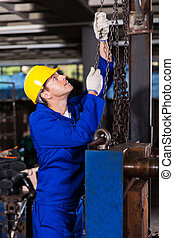 industrial worker pulling chains