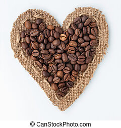 Heart of burlap and coffee beans lying on a white...