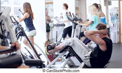 Man Workout - Young man doing exercises in a gym, workout
