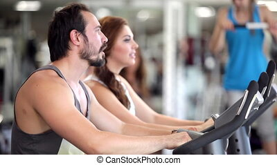 Using Exercise Bikes - People use exercise bicycles in a gym...