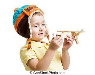 kid boy dressed pilot looking at wooden airplane toy