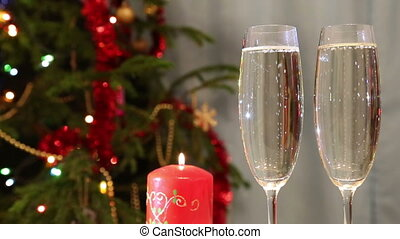 glasses with champagne and candle against christmas tree...