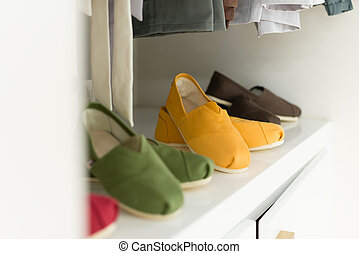 Casual clothes on hangers and shoes at shop. - Row of new...