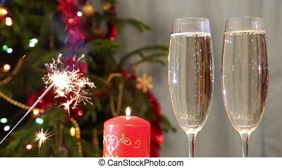 glasses with champagne, candle and sparkler against christmas tree background