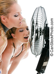 Two blonde woman under fan breeze isolated over white...