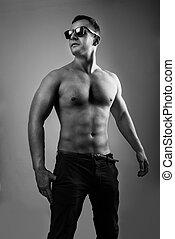 Portrait of muscle man model posing in studio