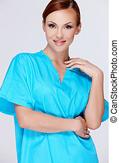 Attractive woman in a turquoise blue shirt standing looking...