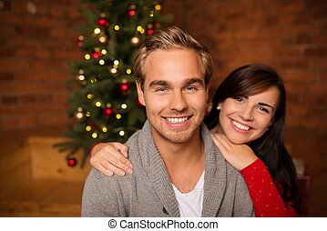 Loving young couple celebrating Christmas standing in front...