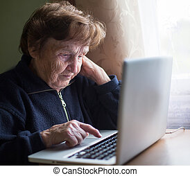 Old woman typing on laptop keyboard