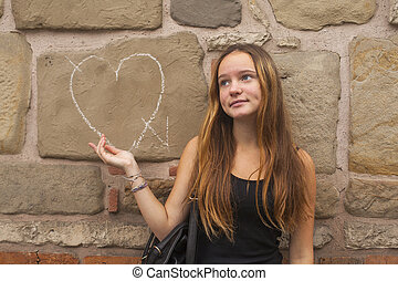 Teen girl in frustration standing against the wall with the...