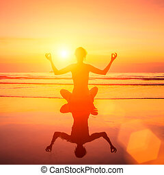 Silhouette of yoga woman on sea sunset with reflection in water.