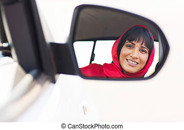 indian female driver looking at side mirror