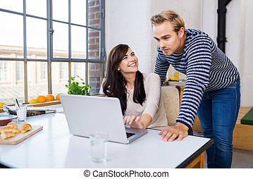 Young couple looking at a laptop in their kitchen on a...