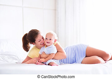 Baby and mother in bed - Young happy mother holding her...