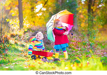 Brother and sister in an autumn park - Cute little children,...