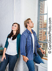 Young couple standing daydreaming in their apartment leaning...