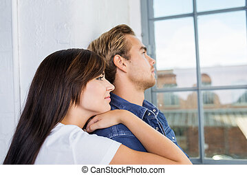 Thoughtful pensive young couple standing staring out of a...