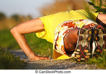 Man doing push-ups during outdoor exercise in summer evening...