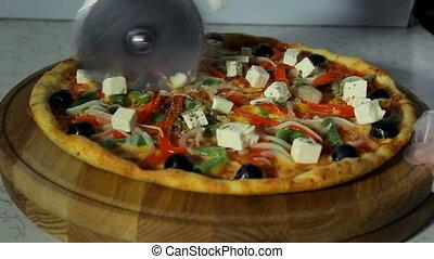 Pizzaiolo slicing pizza