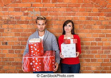 Frowning Lovers Holding Christmas Gifts - Frowning Young...