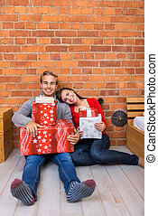 Smiling Sweet Couple Sitting on Floor with Gifts