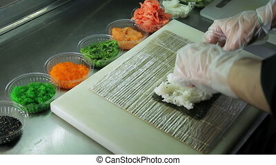 Cook making sushi rolls