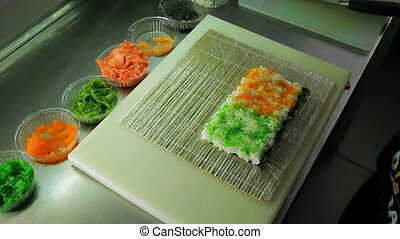 Rolling up the sushi roll with red and green tobiko, upside...