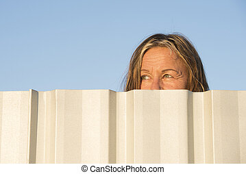 Woman watching eyes behind fence outdoor - Portrait of woman...