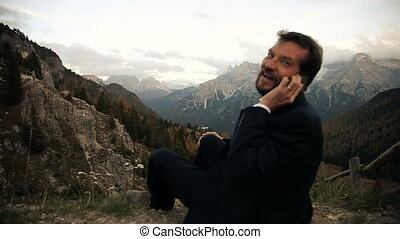 Business man in the mountain - Cool business man talking in...