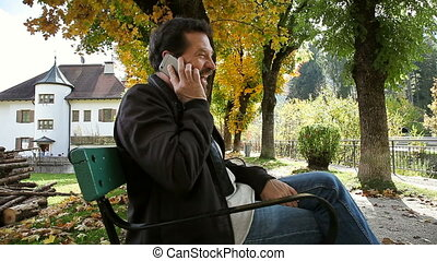 Happy man in autumn on the phone