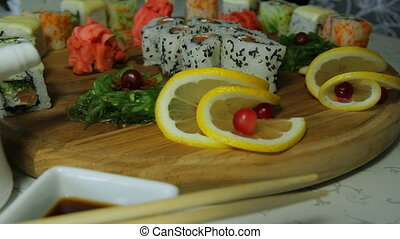 Dolly shot of delicious sushi rolls on wooden plate with...
