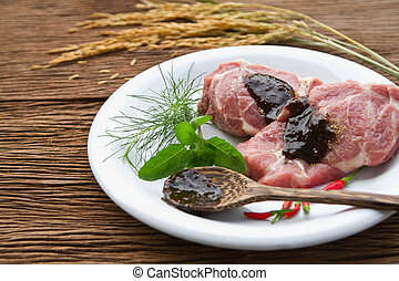 Raw pork steak with green stuff and red chili , black pepper...