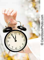 Child's hand holding a alarm clock. Focus on the clock. The Fest
