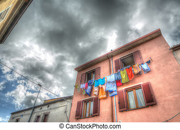 laundry line with colorful clothes in a pink building in hdr ton