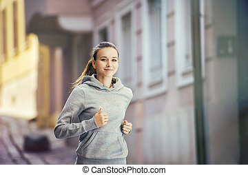 Young woman running in city center - Young female runner is...
