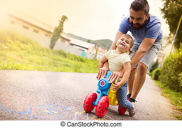 Father and daughter on motorbike in park - Young father with...