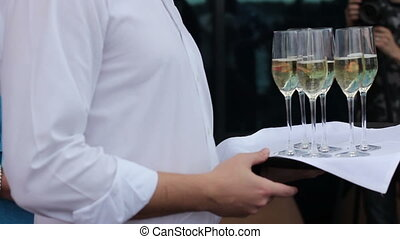 Waiter offer a glass of champagne on a tray can be used for...