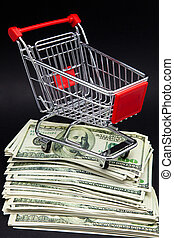 shopping cart on a pile of banknotes of one hundred dollars