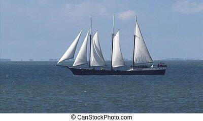 Three-masted sailing ship sailing + zoom out small beach at...